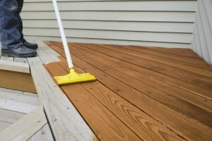 Painter using sponge applicator to apply stain to deck.